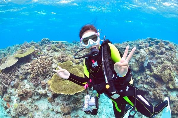 沖縄の珊瑚礁と女性モデルのダイバー
